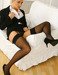 Breathtaking blonde in smart black suit with tiny skirt and sexy stockings.
