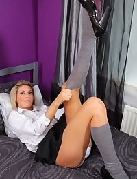 Nicole shows just what a naughty girl she has been as she strips out of her college girl and poses in just her socks.