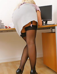 Busty blonde Frankie stays behind after work and slips out of her sexy grey suit leaving her in gorgeous stockings and suspenders.