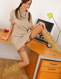 Lovely Nadia E teases us in her office as she slips off her beautiful minidress to reveal her sexy beige stockings and suspenders