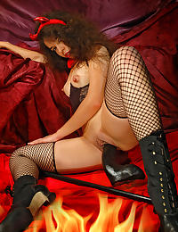 A she devil in black fishnet stockings plays with a giant black dildo