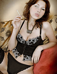redhead beauty posing with a black corset , black stockings using a dildo while she smokes