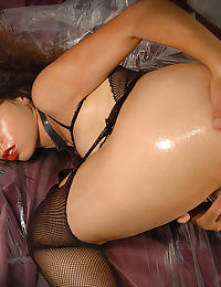 A brunette possing sexy and wet in black stockings and a leather corset